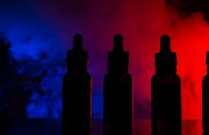 Fluid for electronic cigarettes with a background of a colored cloud of smoke